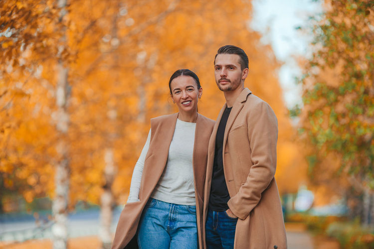 Rear view of couple standing against trees during autumn