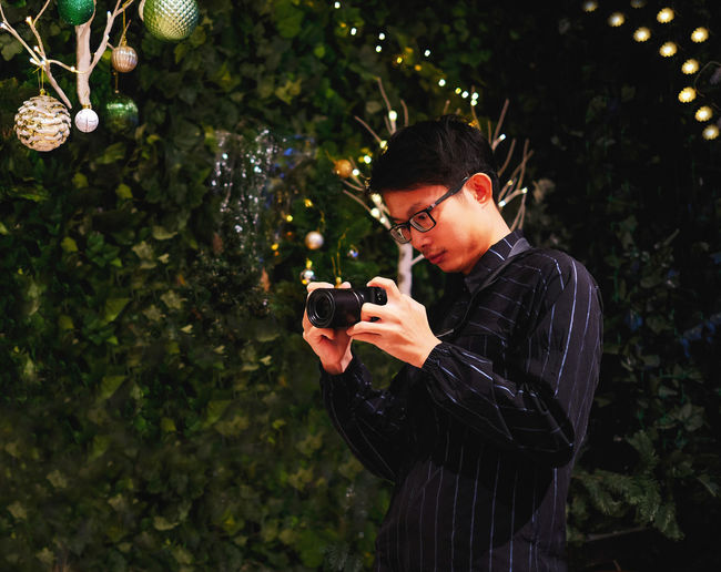 Young photographer take pictures on Christmas day One Person Young Adult Waist Up Lifestyles Leisure Activity Nature Outdoors Young Men Plant Christmas Day Photography Photographer Taking Photos Taking Pictures Asian  Thai Boy Eyeglasses  Glasses Festival Professional Shooting Hanging Decoration