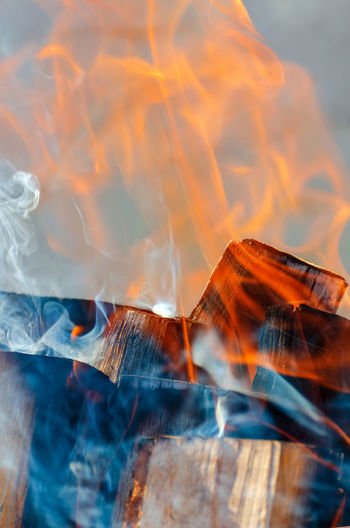 Smoke and fire from burning logs. close up. vertical photo