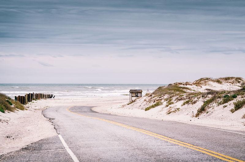 Empty road along sandy landscape