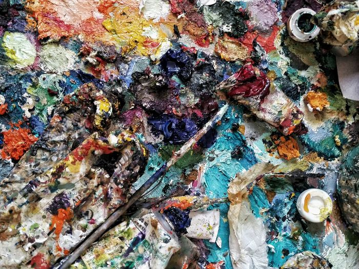 High angle view of paintbrush on colorful messy paint