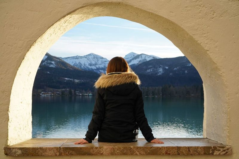 Rear view of woman sitting on arched window over lake against mountains and sky