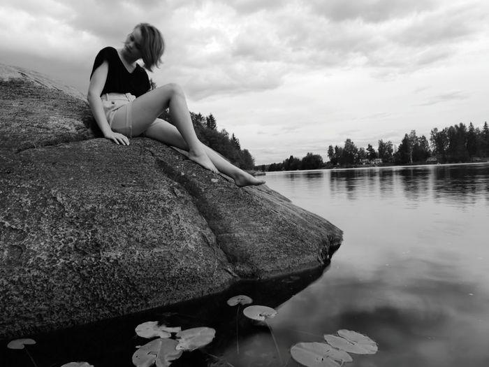 Girl Sitting On Rock In Lake Against Sky
