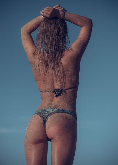 Rear view of woman wearing bikini standing against clear sky