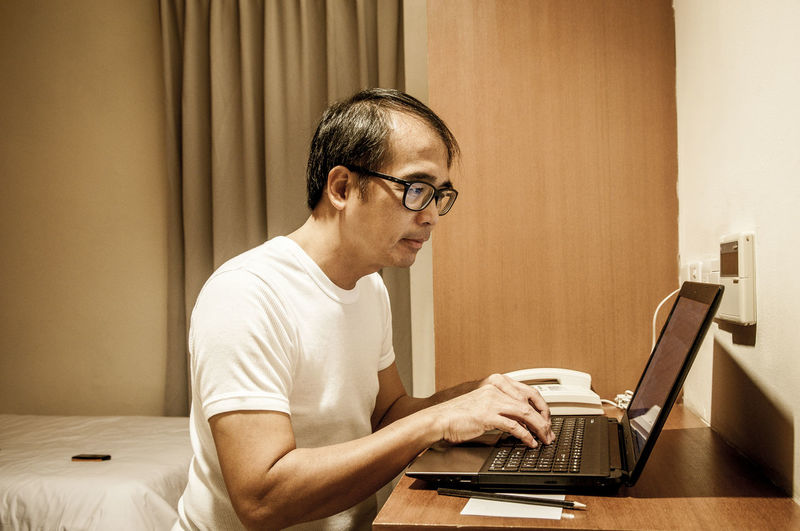 Adult male using laptop in bedroom Adult Asian  Bedroom Computer Indoors  Internet Addiction Laptop Lifestyles Male Man One Person People Sitting Soho Tech Technology Using Work From Home Working