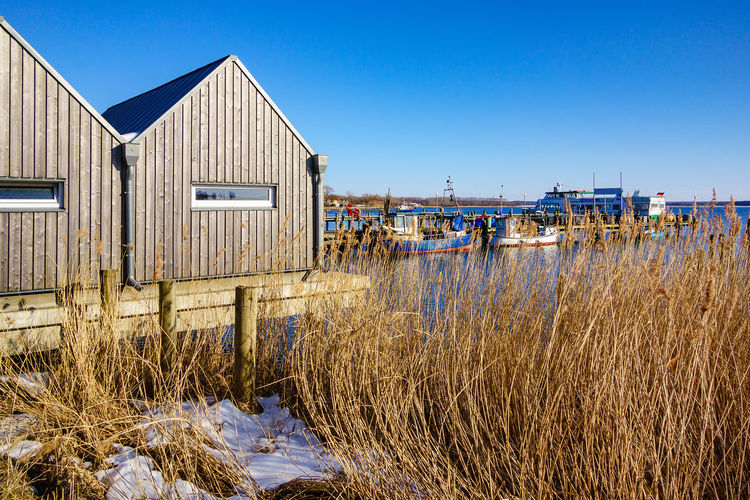 View to the port in Rerik, Germany. Harbor Relaxing Rerik Salzhaff Architecture Blue Boat House Boats Building Exterior Built Structure Clear Sky Day Fishing Boat Nature No People Outdoors Reeds Ships Sky Tourism Travel Destinations Vacation Water
