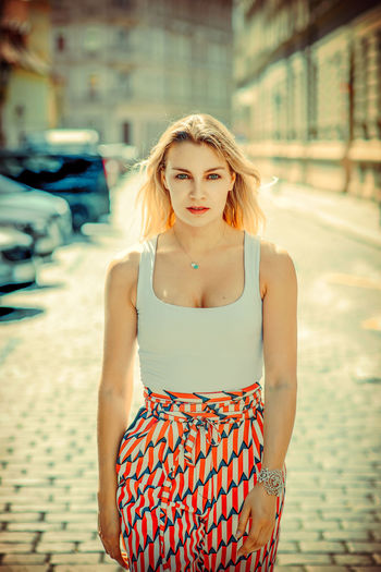 Portrait Of Beautiful Young Woman Standing On Sidewalk In City