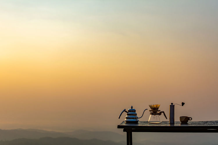 View of tea pot on table against sky during sunset