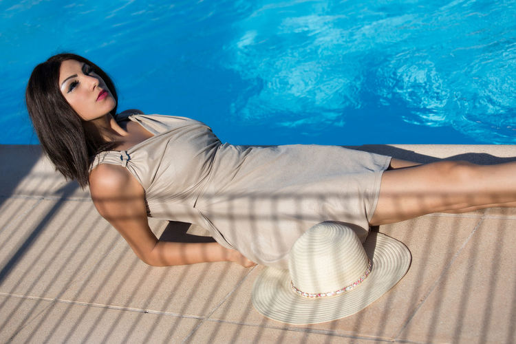 Young Woman Relaxing By Swimming Pool