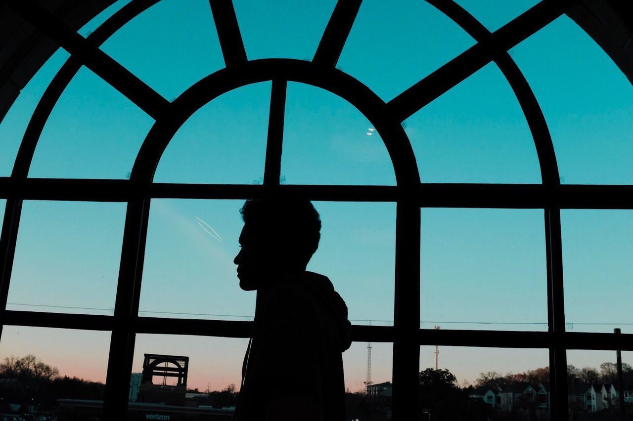 LOW ANGLE VIEW OF SILHOUETTE MAN STANDING BY WINDOW AGAINST SKY