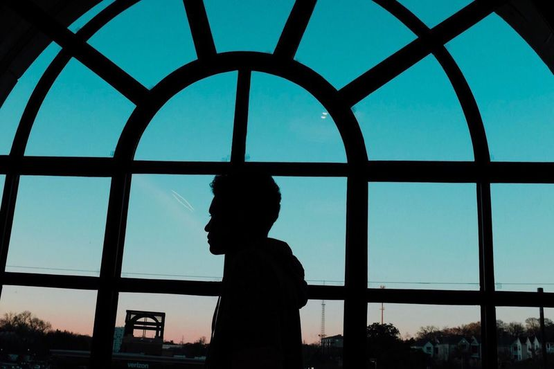 Low angle view of silhouette man looking through window