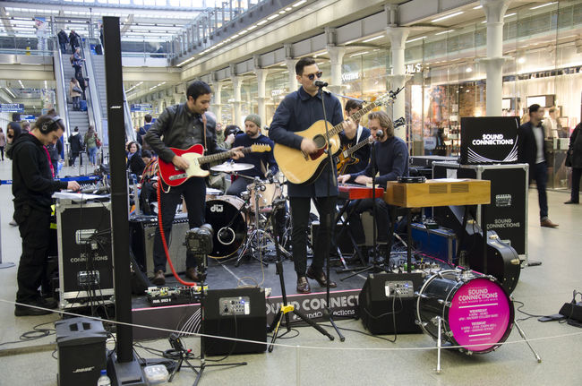 Gaspard Royant - a band performing at a pop-up stage in St Pancras International Railway Station. Band Concert Entertainment Gaspard Royant Group Guitar Guitarist Guitars Instruments Men Music Perform Performance Play Playing Pop-up Concert Rock Sing Singer  Singers Songs Songwriter Stage Vocals