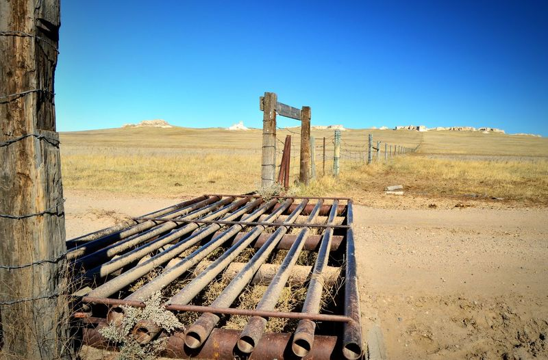 Fence line towards rocks Outdoors Shadows Rock Formation Horizon Over Land Grass Pasture Auto Gate Wooden Posts South Of Lusk Wyoming Wide Open Spaces Clear Sky Countryside Sunny