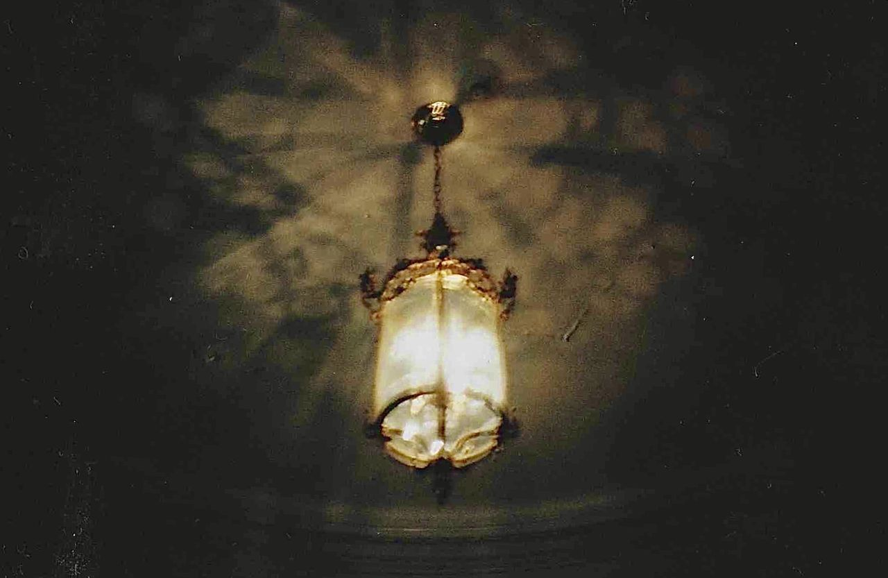 LOW ANGLE VIEW OF ILLUMINATED PENDANT LIGHT HANGING FROM WALL