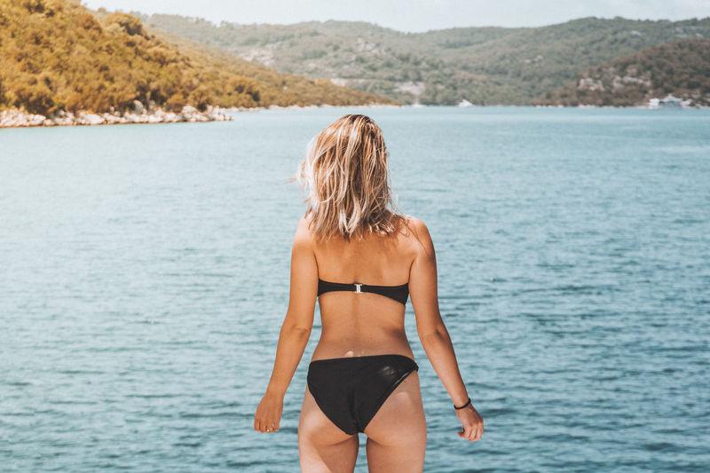Rear view of woman wearing bikini standing against sea