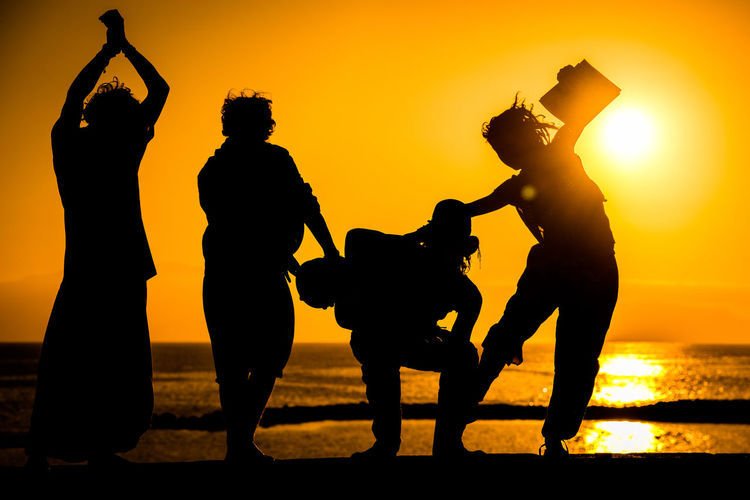 Silhouette friends at beach against sky during sunset