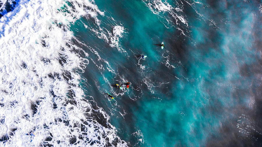 High angle view of surfers in the sea.