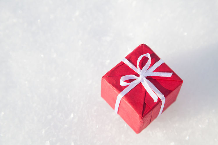 Small Christmas gift box on white snow background Box Celebration Christmas Christmas Decoration Christmas Present Close-up Copy Space Gift Holiday Holiday - Event No People Outdoors Paper Parcel Present Red Ribbon - Sewing Item Single Object Snow Snowflake Snowing Tradition Winter Wrap Wrapped
