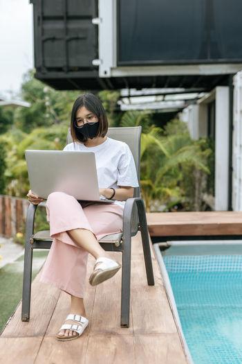 Woman using mobile phone in swimming pool