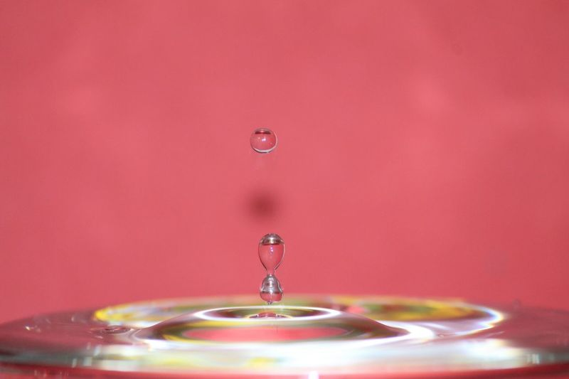 Close-up of drop falling in water against red wall