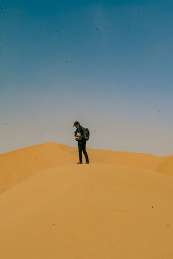 Man standing on sand dune in desert against sky