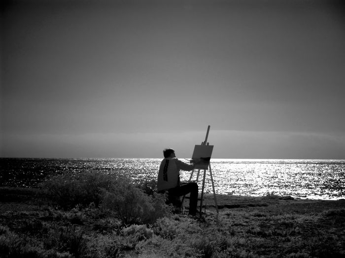 Man Painting On Canvas While Sitting On Field By Sea Against Sky