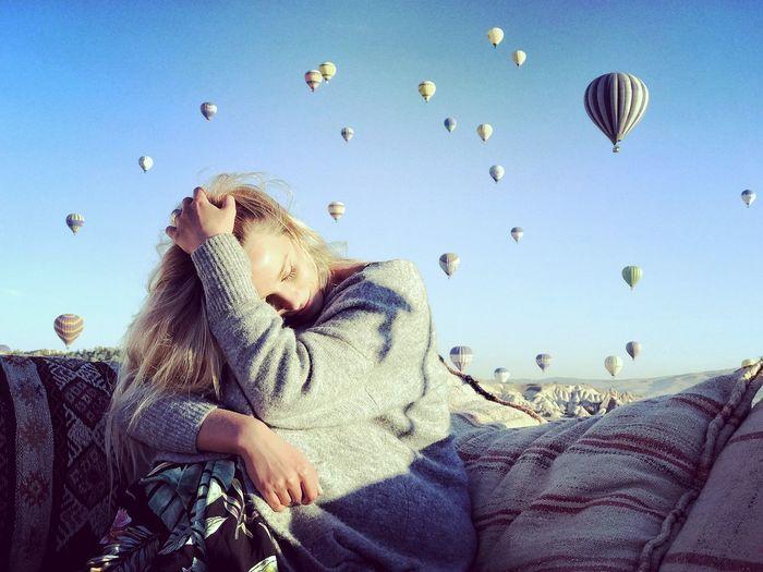 Woman sitting against hot air balloons