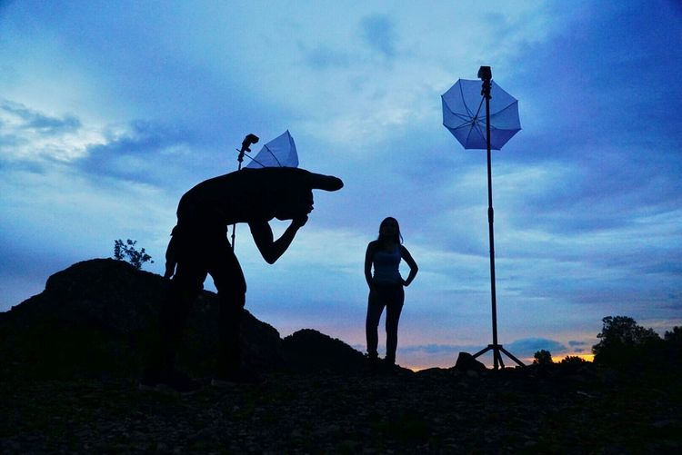 Silhouette Photographer Taking Picture Of Model At Outdoors