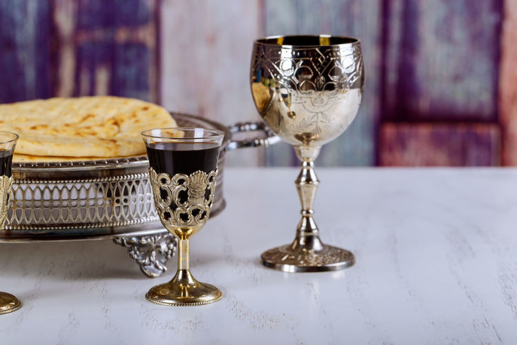 Taking Communion. Cup of glass with red wine, bread on wooden table close-up. Focus on wine Bread Christian Christianity Church Communion Cross Jesus Jesus Christ Pray Sacrament Spirituality Worshiping God Bible Blood Crucifix Cup Eucharist Gospel Holy Pastor Prayer Religion Sacrifice Spirituality, Wine