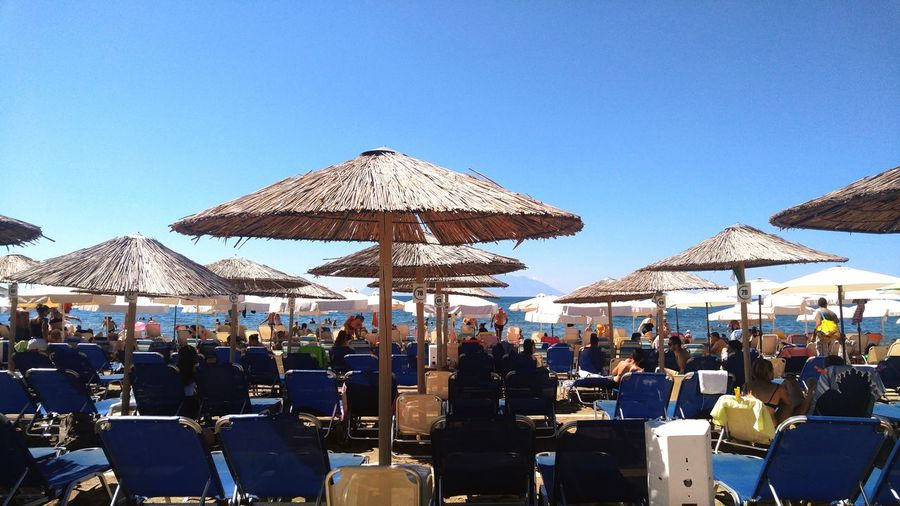 Group of people in restaurant at beach against clear blue sky