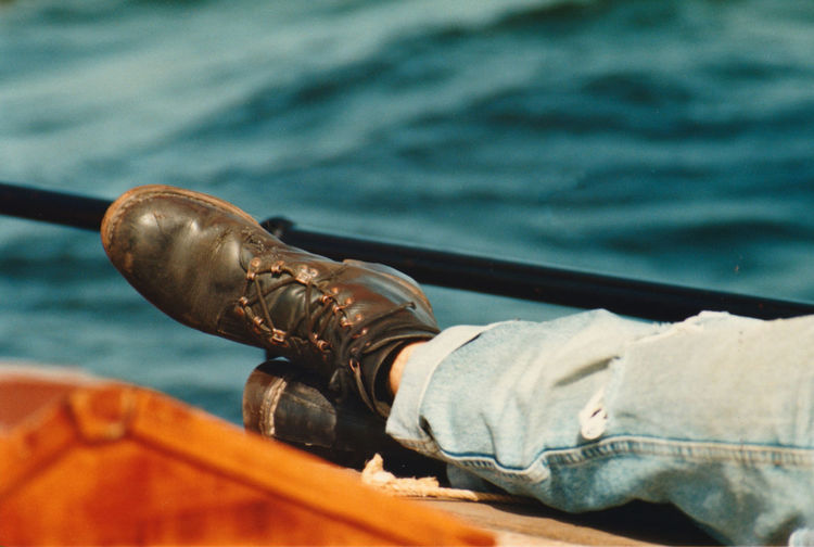 Low section of person wearing shoes sitting on boat deck