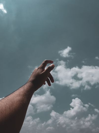 Low angle view of man hand against sky