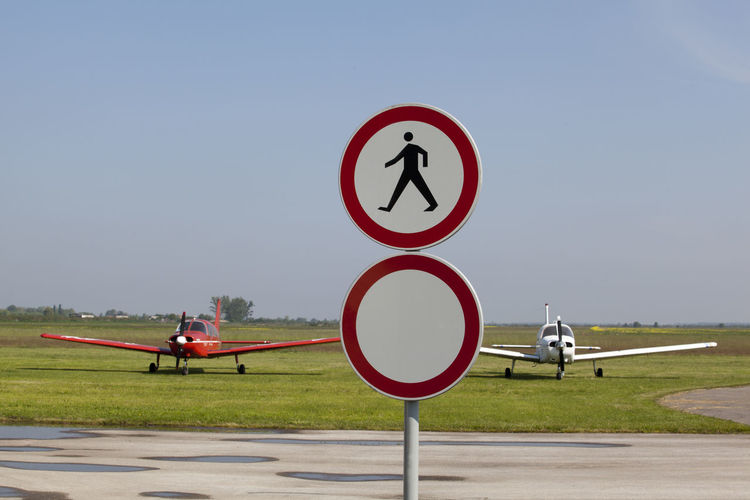 Road sign at airport runway against clear sky