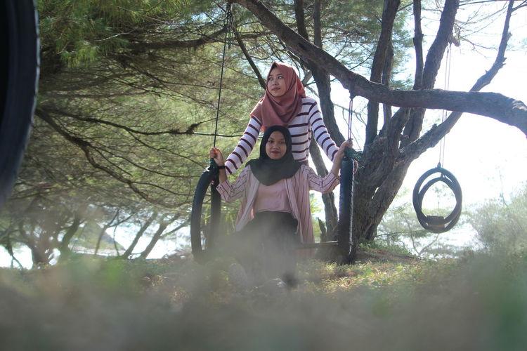 Full length of girl sitting on swing with sister against tree
