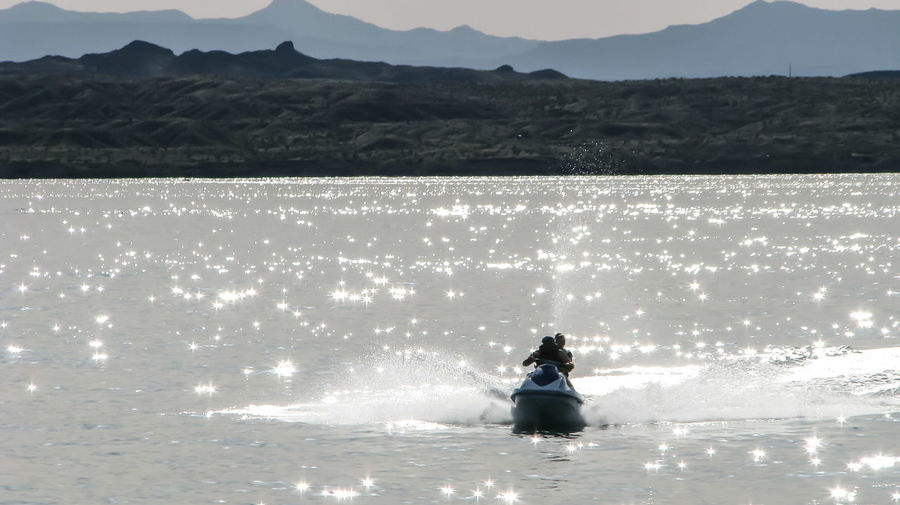 Man with woman riding jet boat on lake