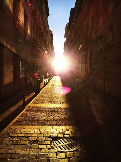 Cobblestone street in city during sunset