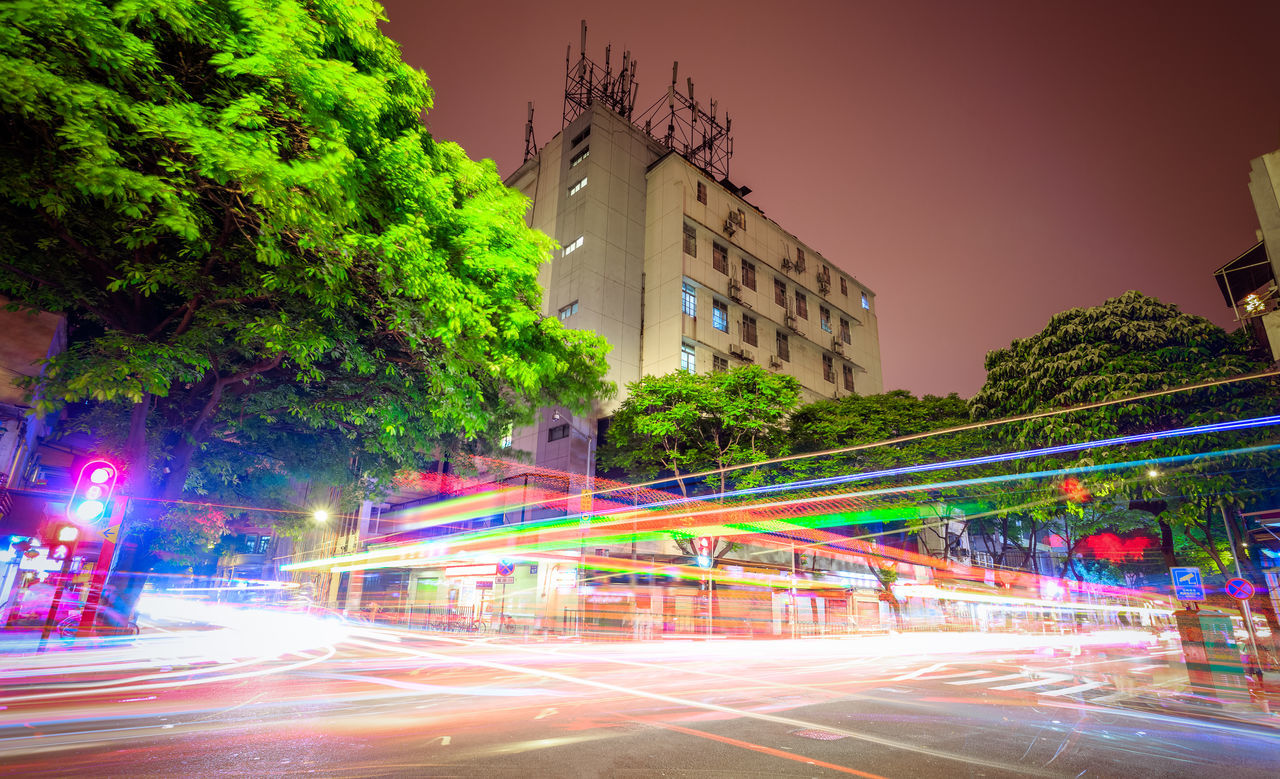 street, speed, architecture, long exposure, building exterior, city, light trail, motion, night, illuminated, road, built structure, outdoors, tree, transportation, blurred motion, clear sky, street light, multi colored, no people, sky, high street