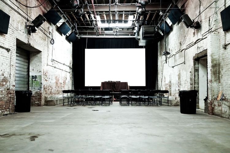 Empty chairs against projection screen in old auditorium