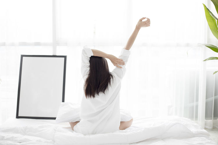 Woman stretching hands on bed