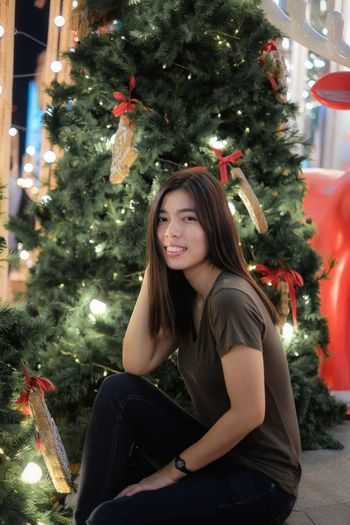 Portrait of young woman by illuminated christmas tree