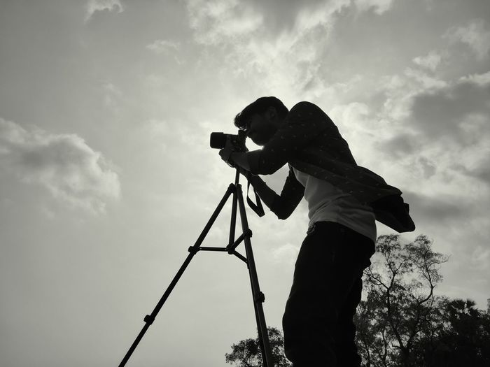 Side view of silhouette man photographing against sky