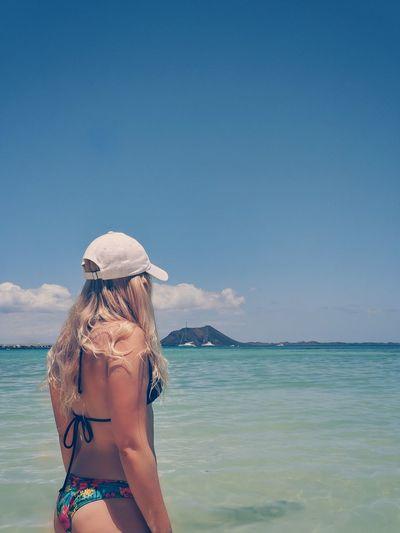 Rear view of young woman wearing bikini standing at beach