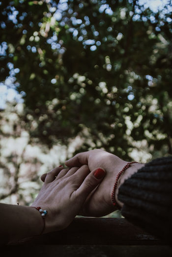 Cropped image of people holding hands outdoors