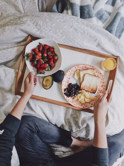 High angle view of woman having breakfast on bed