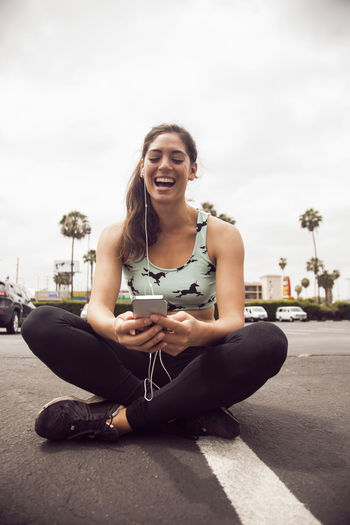 Happy young woman using phone while sitting on camera