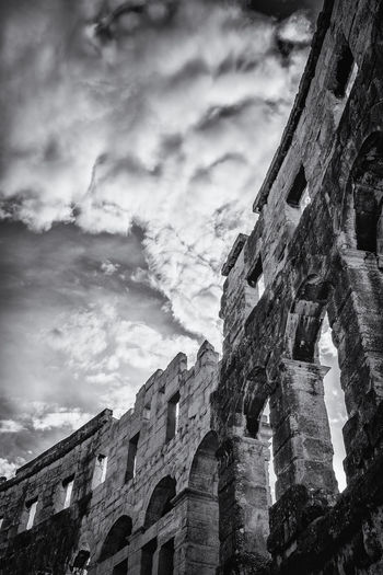 Low angle view of old ruin building against cloudy sky