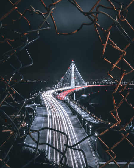 View of light trails on bridge seen through chainlink fence at night