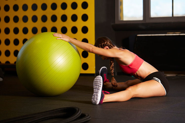 Side view of woman exercising with fitness ball while sitting on floor in gym