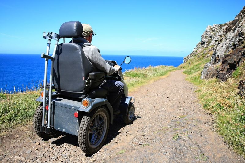 Rear View Of Man Sitting On Vehicle By Sea During Sunny Day