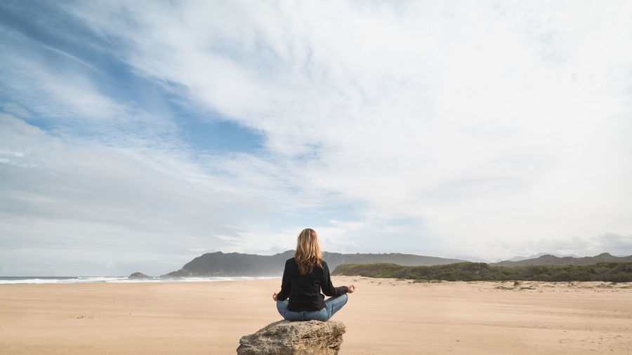 Rear view of woman meditating on beach